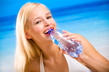 Young beautiful happy woman with bottle of water on beach